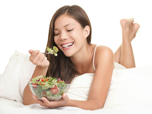 Stock Photo Featuring a Happy Woman Eating a Salad While Laying Down