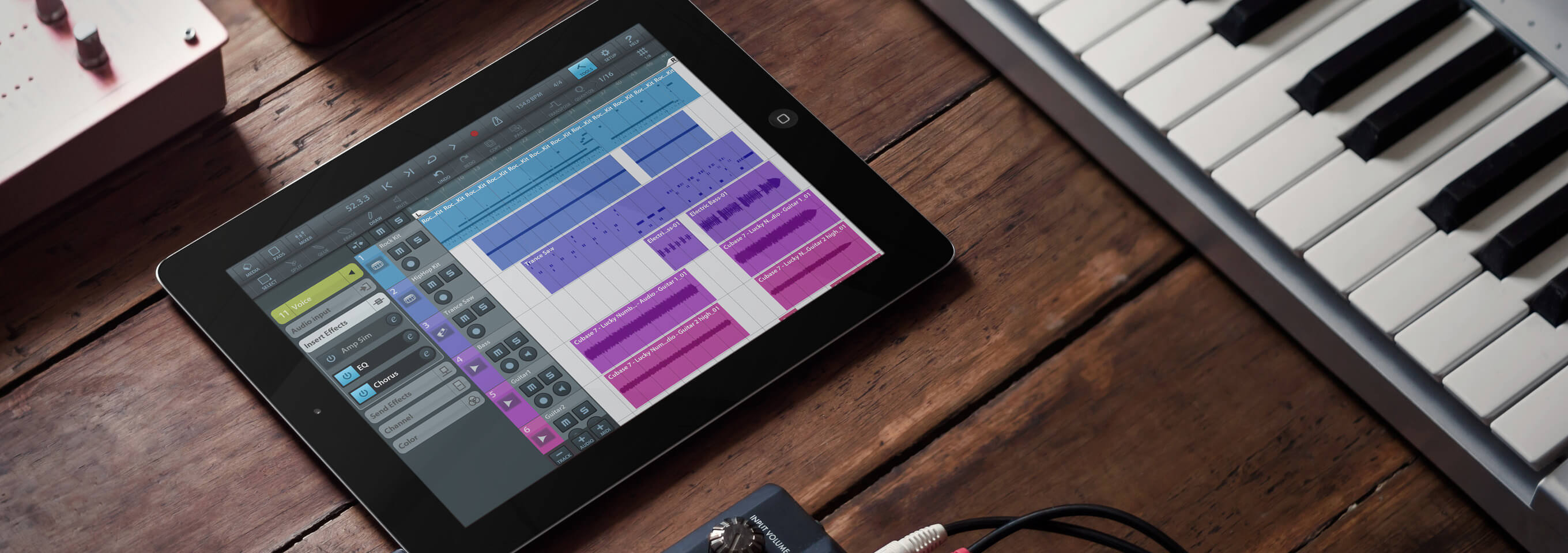 iPad Mockup on a Table Next to a Keyboard Featuring a Music Recording App in its Screen