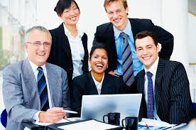 Stock Image of a Group of Business Executives Gathered Around a Computer and Laughing