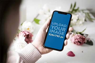 Mockup Of A Woman Holding An Iphone 11 By Some Valentine S Day Gifts