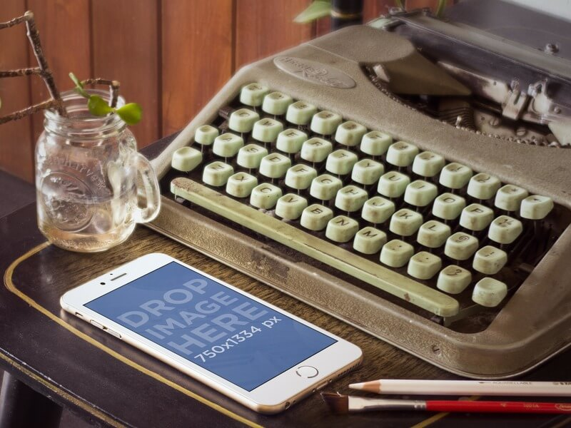 Mockup of Gold iPhone 6 Next to Vintage Typewriter