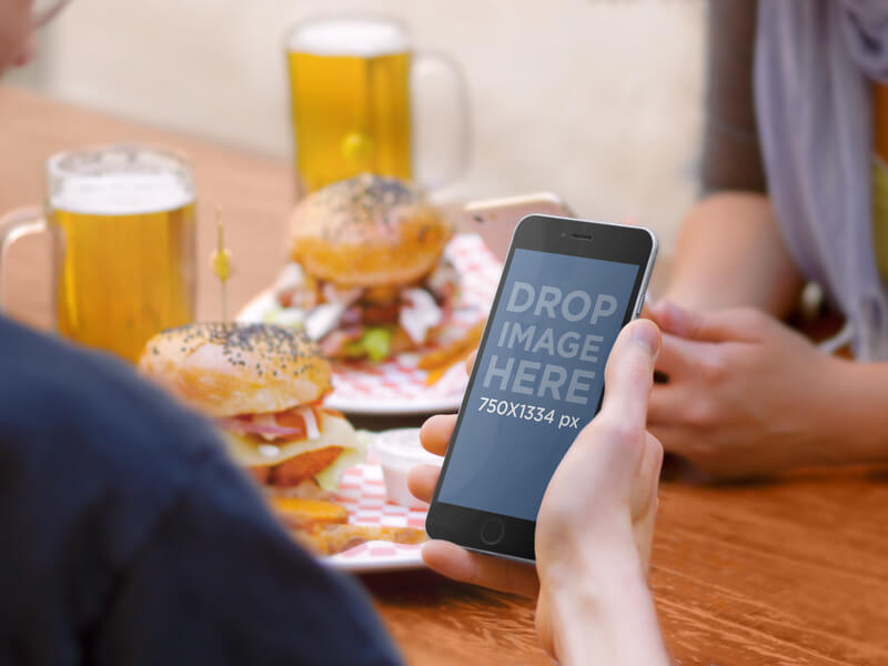 IPHONE 6 MOCKUP AT A HAMBURGER AND BEER PLACE WITH FRIENDS