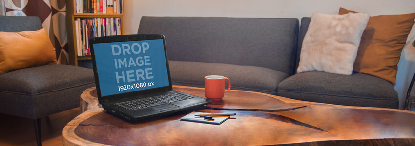 Mockup of a Black Laptop On Top of a Wooden Coffee Table