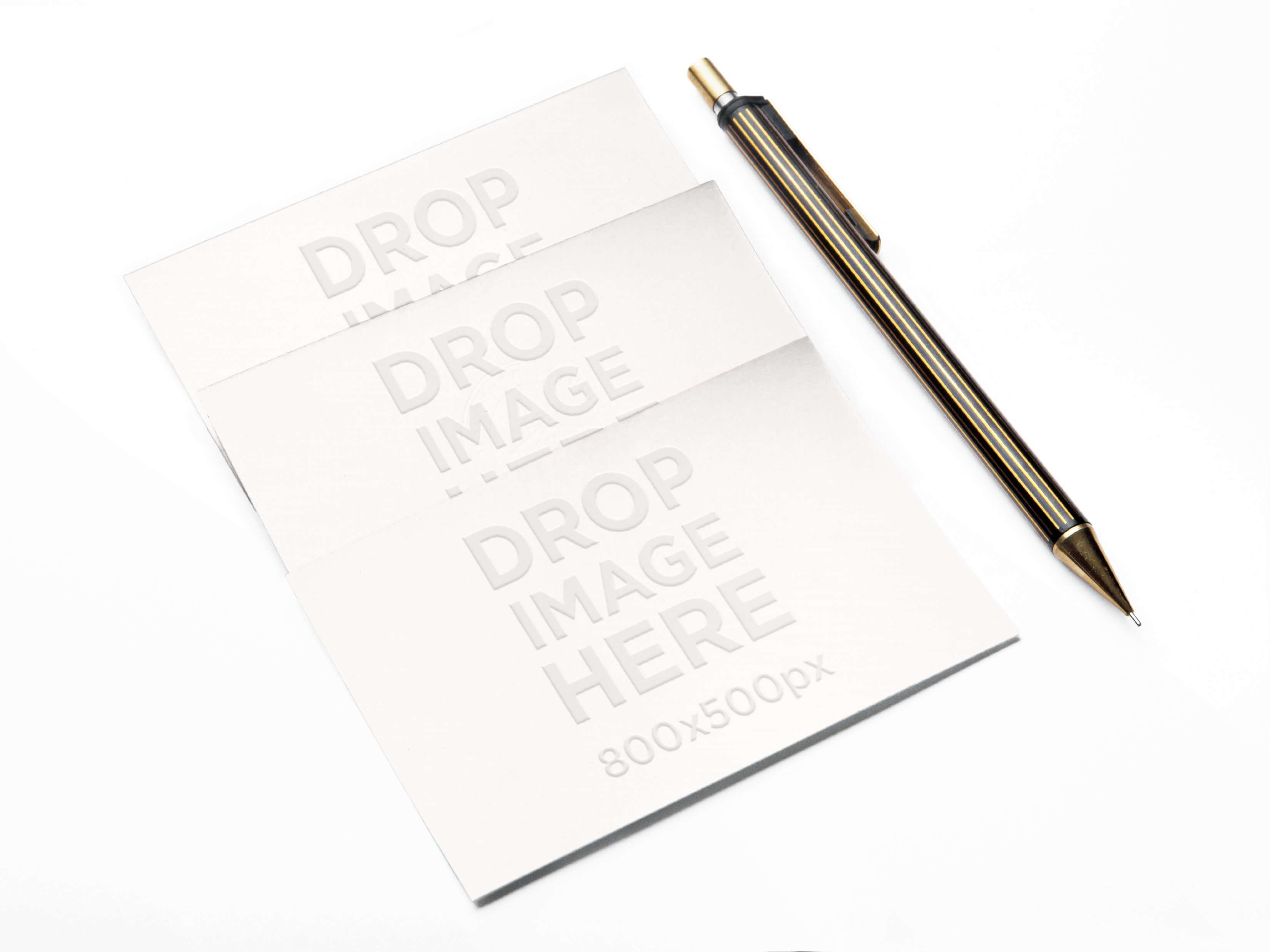 MOCKUP OF 3 BUSINESS CARDS LYING NEXT TO A METALLIC PEN