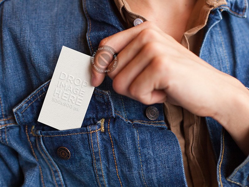 MOCKUP OF A WOMAN PLACING A BUSINESS CARD IN HER JACKET'S FRONT BAG