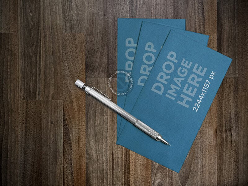 MOCKUP FEATURING A SET OF BUSINESS CARDS LYING NEXT TO A PEN ON A DESK