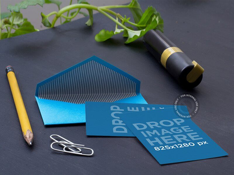 MOCKUP OF AN OPEN ENVELOPE LYING NEXT TO SOME OFFICE SUPPLIES