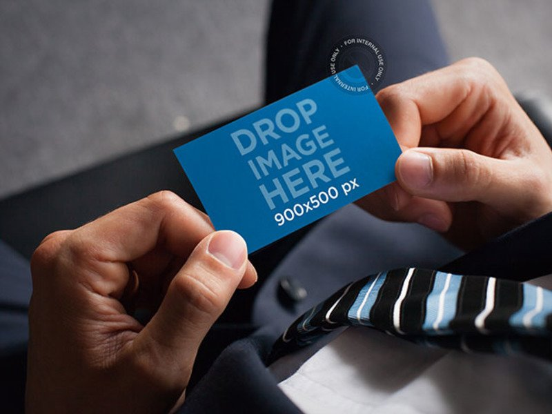 BUSINESS CARD MOCKUP FEATURING A BUSINESSMAN HOLDING A BUSINESS CARD