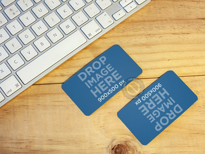 MOCKUP OF TWO BUSINESS CARDS LYING ON TOP OF A DESK AT AN OFFICE