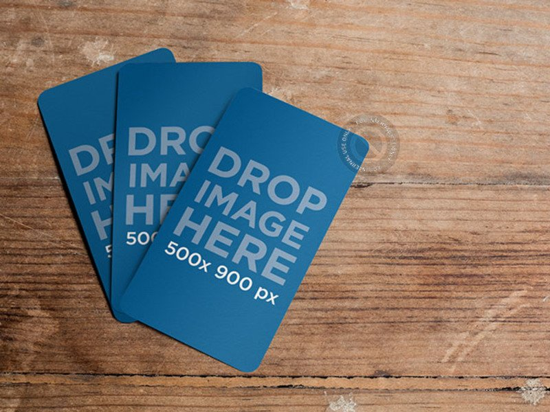 MOCKUP FEATURING THREE BUSINESS CARDS LYING ON TOP OF A WOODEN TABLE