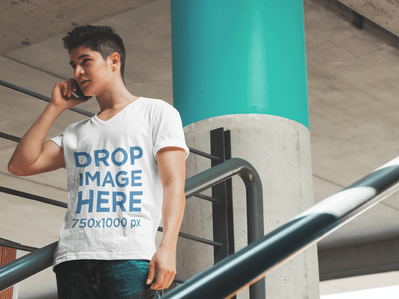 T-SHIRT MOCKUP OF A YOUNG MAN TALKING ON THE PHONE