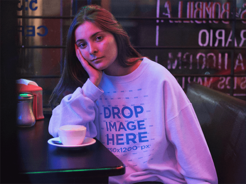 Crewneck Mockup Featuring a Lovely Girl Waiting in a Late Night Cafe