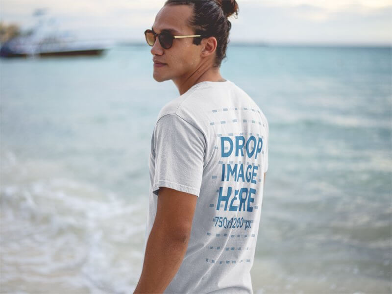 T-Shirt Mockup of a Hipster Guy Wearing Sunglasses at the Beach Shore