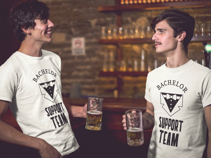 Two dudes having a beer at the bar while wearing different bachelor party tshirts template
