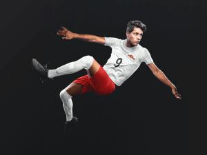 Custom soccer jersey logo mockup of a man doing a scissor kick