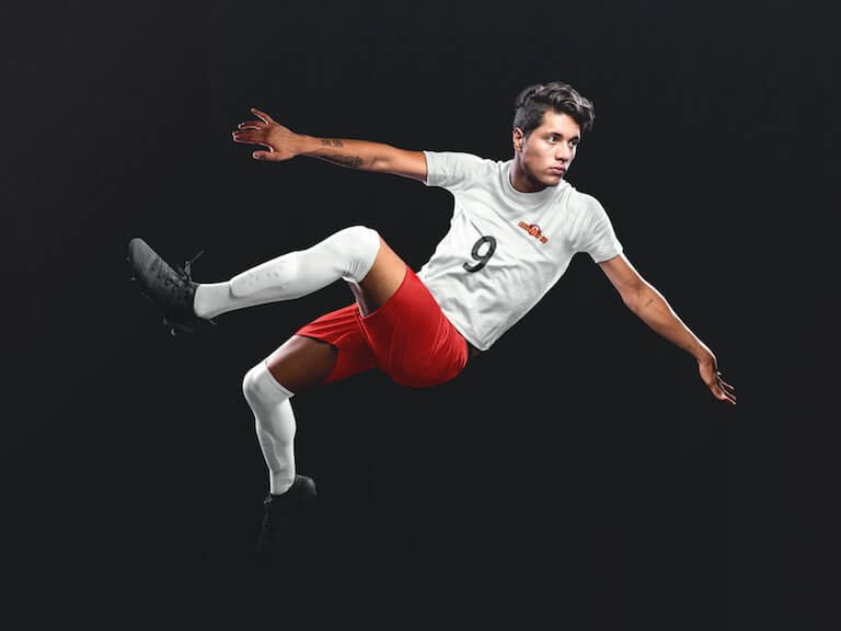 Custom soccer jersey logo mockup of a man doing a scissor kick