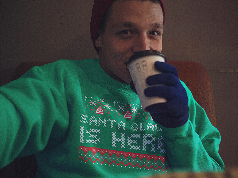 Boy wearing a Ugly Christmas Sweater and Zipping His Coffe