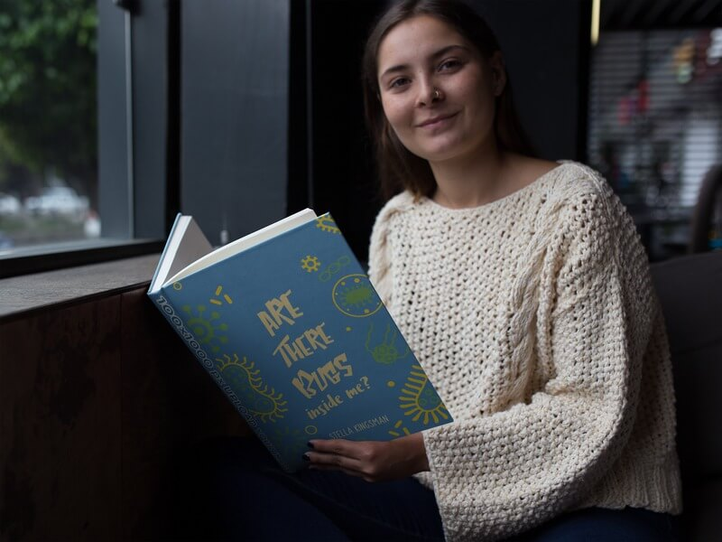 Hardcover Book Mockup Of A Young Woman At Home Reading