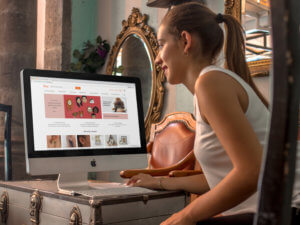 Saleswoman At A Vintage Store Using An Imac Mockup