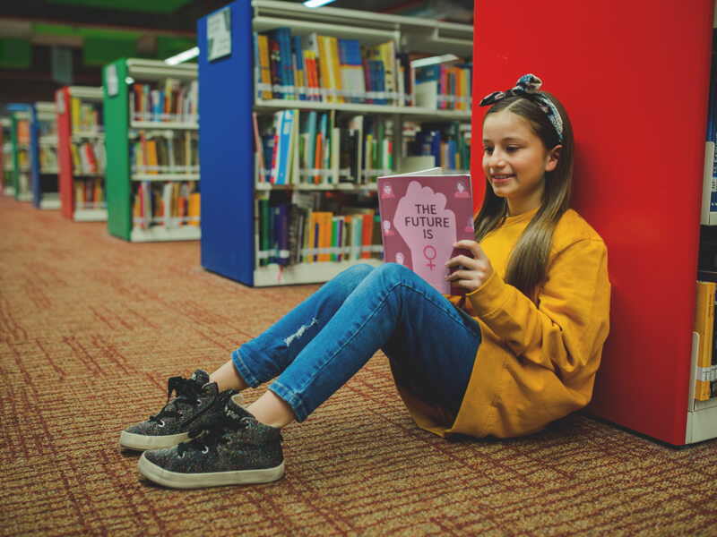 Girl With A Yellow Sweater Reading A Book Mockup Sitting At The Library