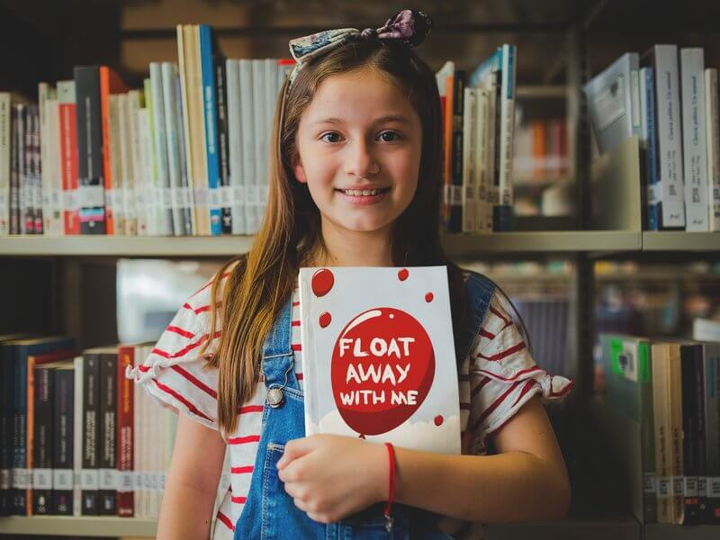 Happy Little Girl Holding A Book Mockup At The Library