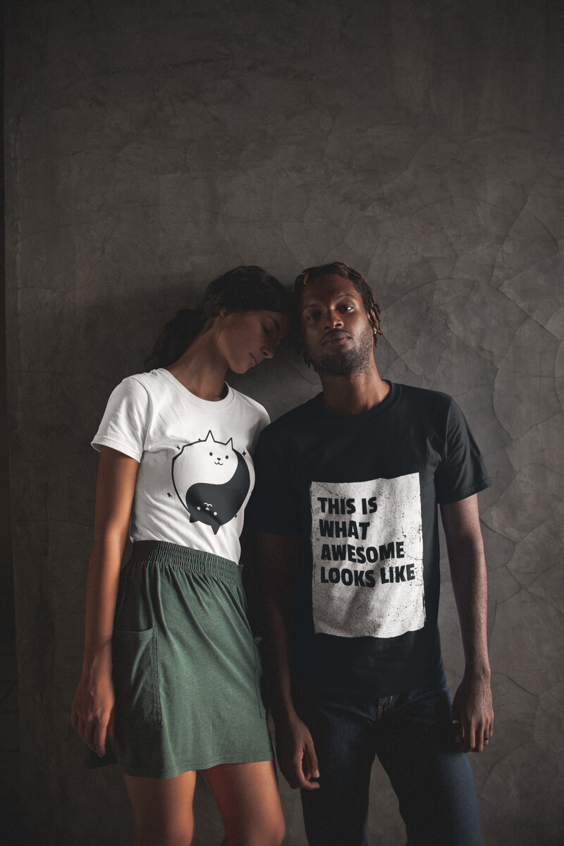 Posing Couple Wearing Interracial T Shirts Mockup Against A Gray Wall
