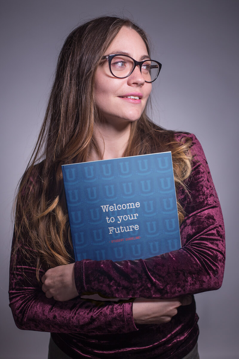 Mockup of a Teacher Holding a Big Book of Welcome