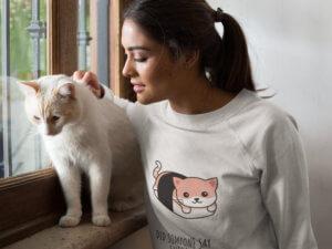 Closeup Of A Beautiful Woman Wearing A Crewneck Sweatshirt Mockup Petting A White Cat Near A Window