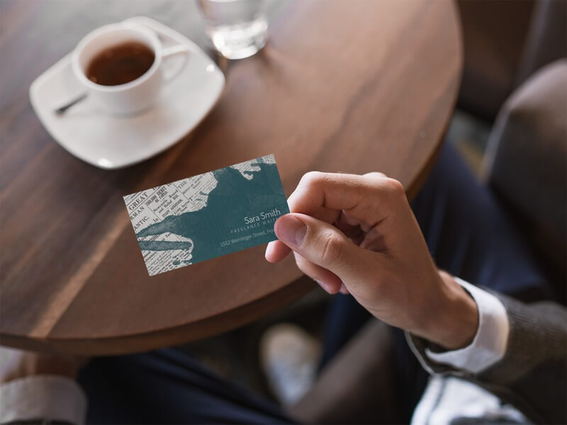 Business Card Being Held While Inside A Cafe