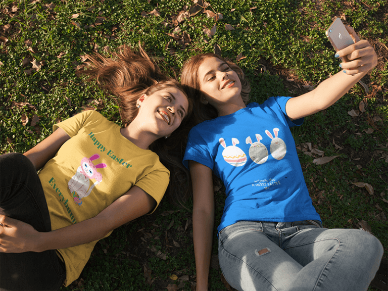 Two Girlfriends Wearing Tees Mockup While Lying On The Grass Taking A Selfie A16280