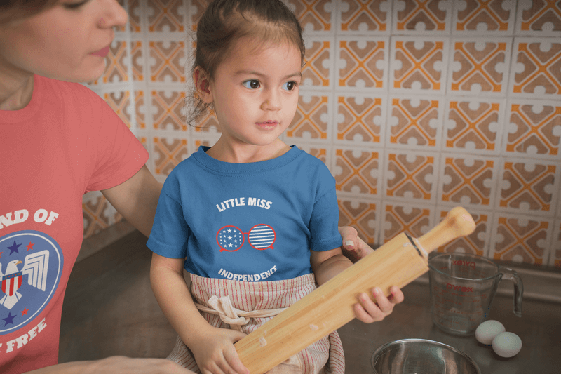 Girl Learning How To Cook Wearing A T Shirt Mockup With A Patriotic Design