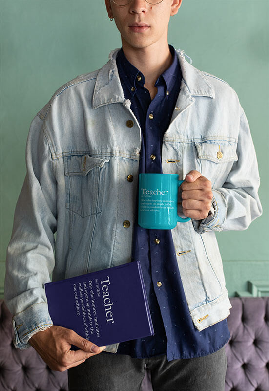 Mockup Of A Man Wearing A Denim Jacket And Holding A Coffee Mug And A Book