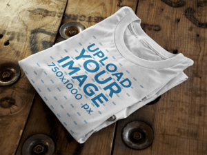Folded T Shirt Mockup Sitting On Top Of A Wooden Table