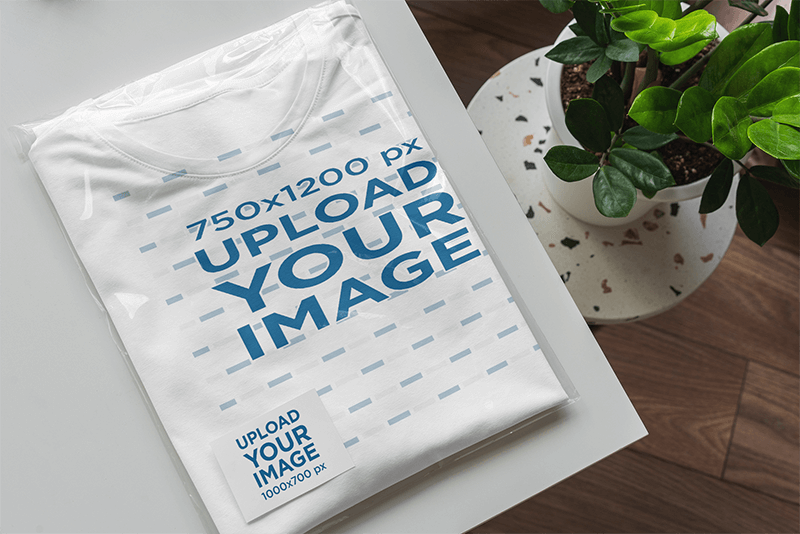 Mockup Of A Folded T Shirt Wrapped In A Transparent Bag With A Business Card Inside