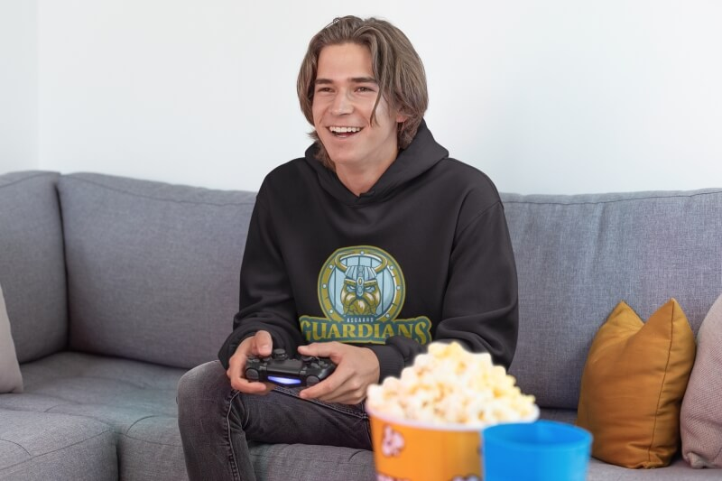 Pullover Hoodie Mockup Of A Joyful Gamer Man Playing Video Games On A Couch