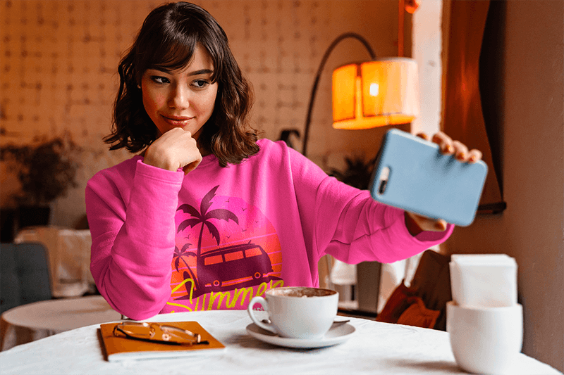 Sweatshirt Mockup Of A Woman Taking A Selfie At A Coffee Shop