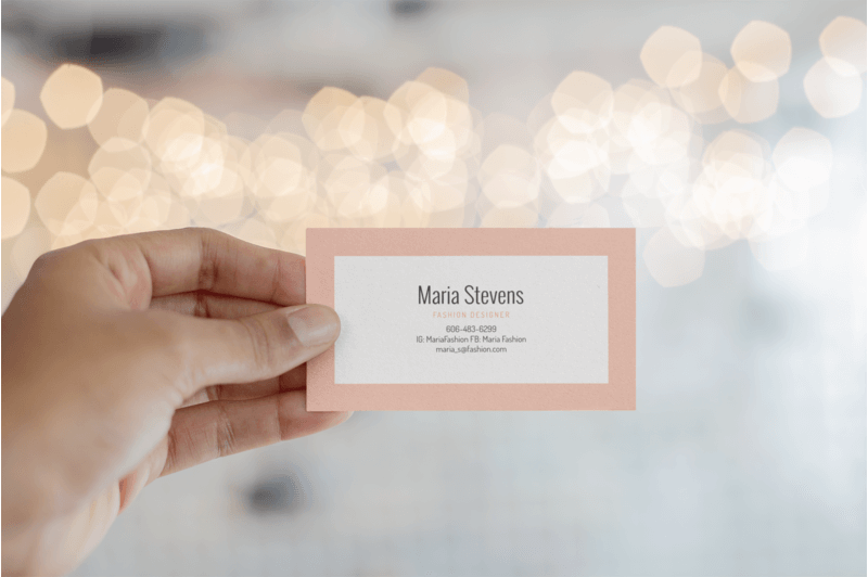 Mockup Of A Business Card Being Held Against Blurred Background