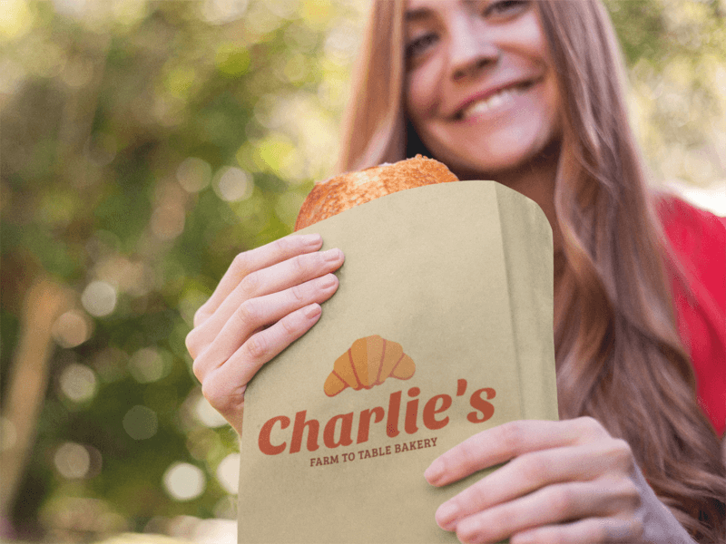 Paper Bag Mockup Featuring A Young Woman Eating A Pastry