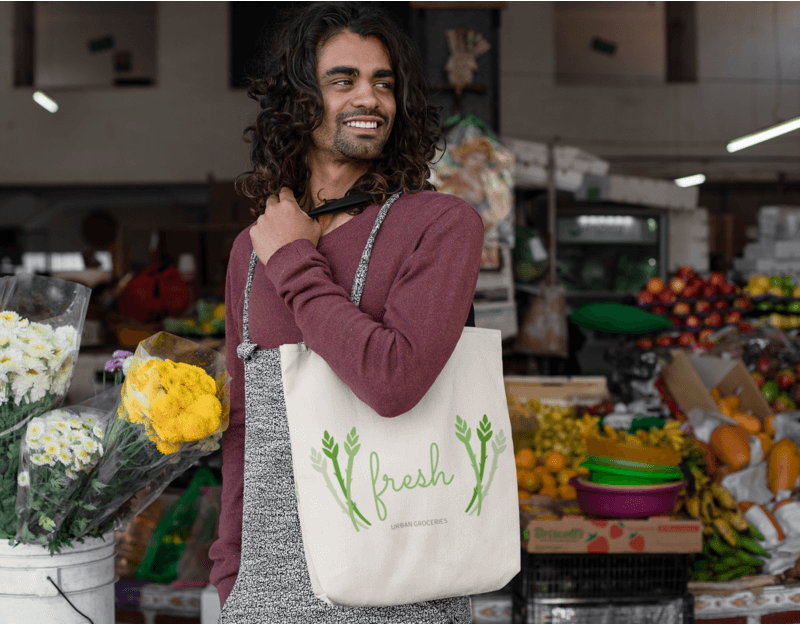Tote Bag Mockup Of A Man With Long Hair In A Food Market