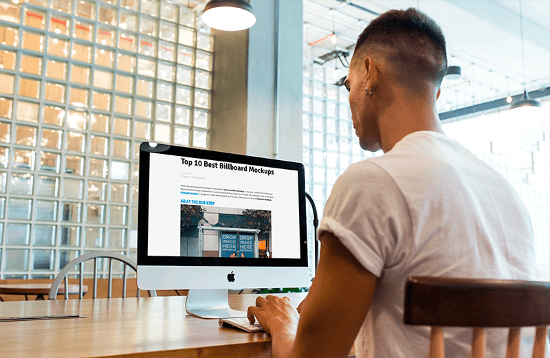 Imac Mockup Being Used By A Man At A Startup