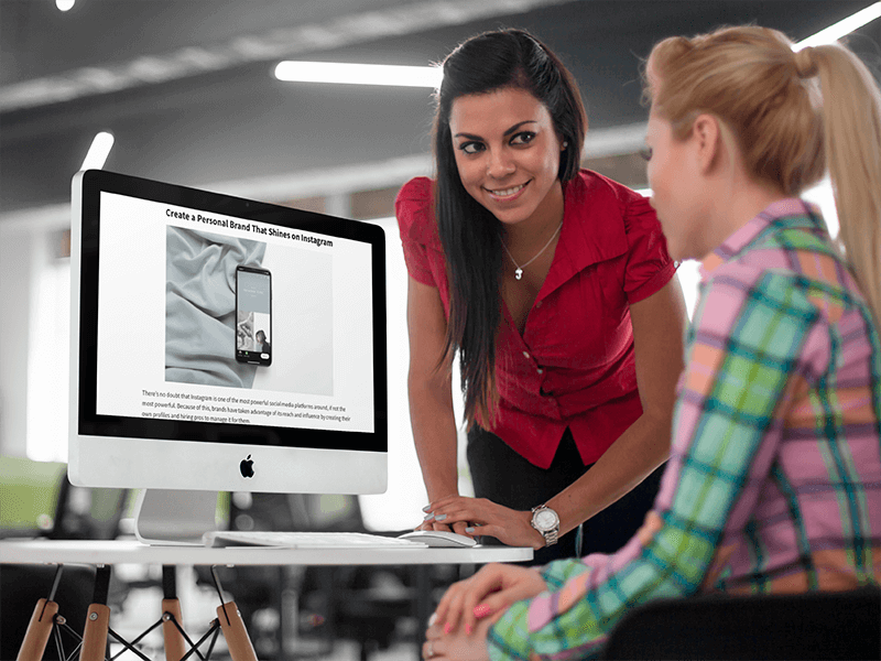 Two Young Businesswoman Chatting In Front Of An Imac Mockuppng