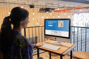 Woman Working With Imac Mockup At Her Workstation