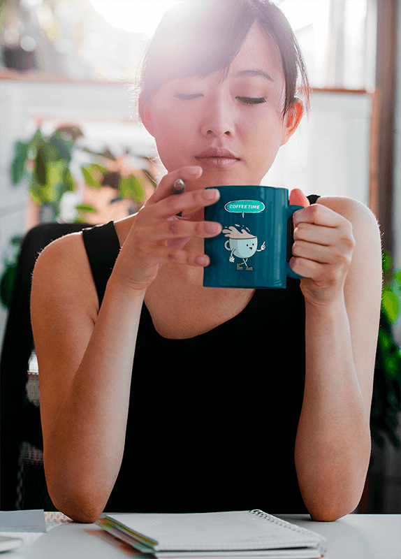 Mockup Of A Woman Drinking From An 11 Oz Coffee Mug While Working