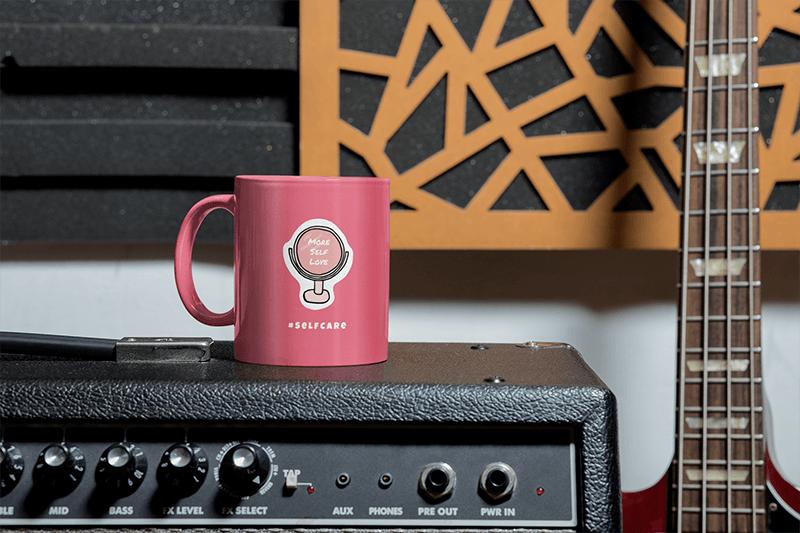 Mockup Of An 11 Oz Coffee Mug Placed Next To A Bass Guitar