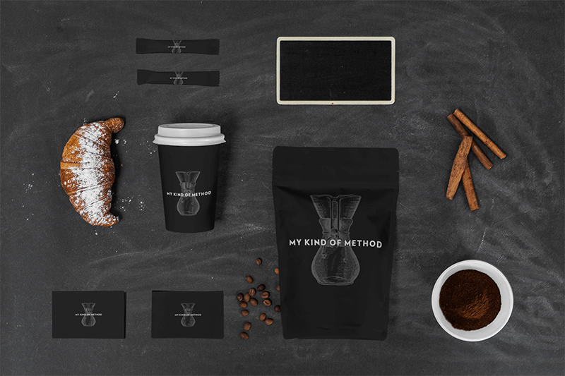Multiple Product Mockup Of A Coffee Cup And Two Sugar Packets Featuring A Zip Bag Next To Some Business Cards