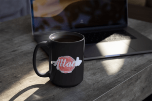 Mockup Of A Sticker On A Coffee Mug Beside A Laptop
