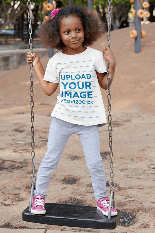 T Shirt Mockup Of A Playful Girl Standing On A Swing