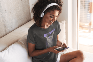 Tee Mockup Of A Smiling Woman Listening To Music At Home