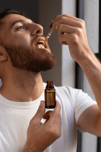 Dropper Bottle Mockup Of A Man Taking Cbd Oil