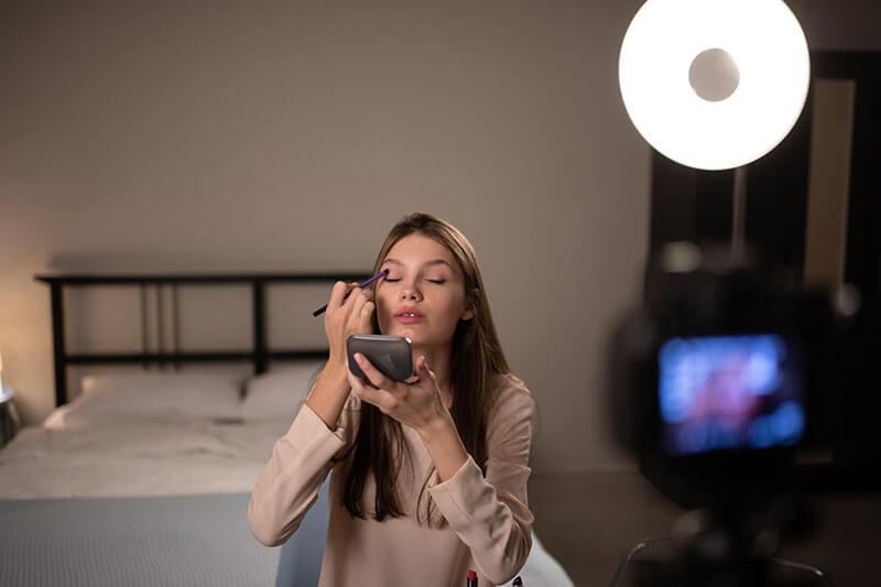 Female Influencer Applying Eyeshadow For Camera